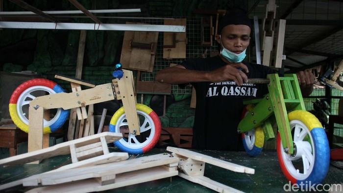 Nugroho (37) pengrajin sepeda keseimbangan (balance bike) merakit sepeda pesanan pelanggan. Sepeda berbahan dasar kayu ini banyak diminati.