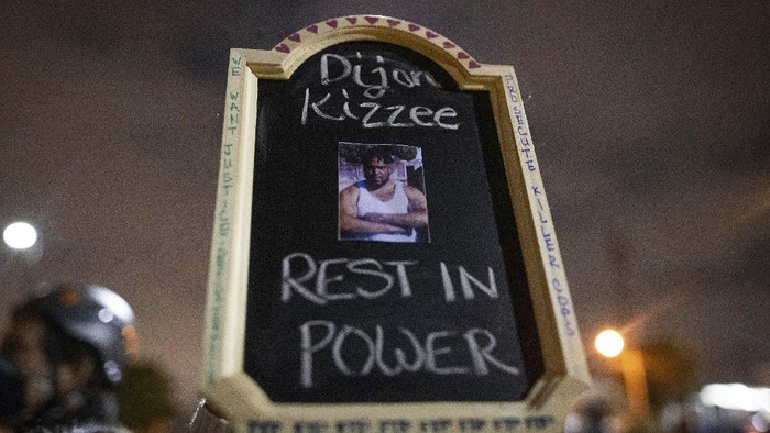 A protester holds a sign with a picture of Dijon Kizzee, who died after being shot by deputies of the Los Angeles Sheriffs Department on Monday, Aug. 31, 2020, in Los Angeles, Calif. (AP Photo/Christian Monterrosa)