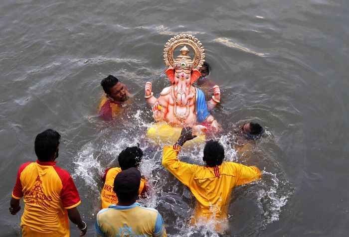 Volunteers immerse an idol of elephant-headed Hindu god Ganesha in the Arabian Sea, marking the end of the 10-day long Ganesh Chaturthi festival in Mumbai, India, Tuesday, Sept. 1, 2020. (AP Photo/Rajanish Kakade)