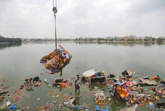 Indian workers remove idols of elephant-headed Hindu god Ganesha that were immersed earlier in  Saroornagar Lake on the final day of Ganesh Chaturthi festival in Hyderabad, India, Tuesday, Sept. 1, 2020. The festival is a celebration of the birth of Ganesha, the Hindu god of wisdom, prosperity and good fortune. (AP Photo/Mahesh Kumar A.)