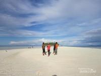 Wisatawan berfoto ria dengan background pulau Koh.