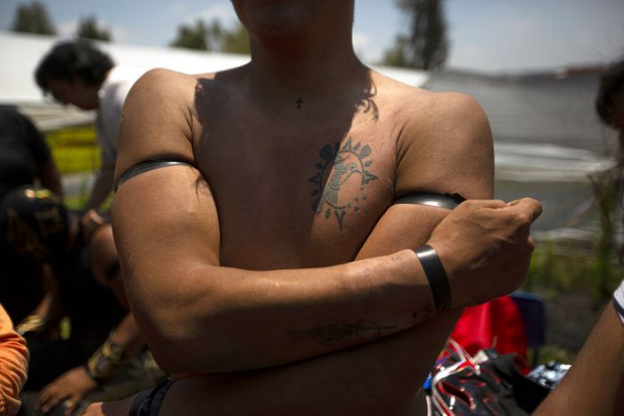 A Mexican Lucha Libre wrestler removes his uniform after an exhibition fight for the media, as he trains for what will be live streaming events which wrestlers will charge for, at Xochimilcos famous floating gardens on the outskirts of Mexico City, Saturday, Aug. 22, 2020, amid the new coronavirus pandemic. According to the fighter known as