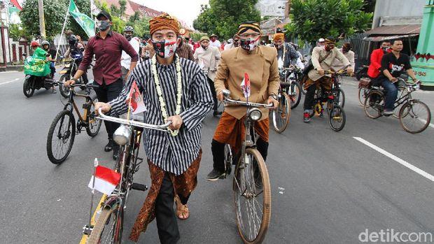 Pasangan Gibran Rakabuming Raka-Teguh Prakosa berangkat ke KPU Solo untuk mendaftar sebagai peserta Pilkada Solo. Gibran-Teguh berangkat naik sepeda onthel.