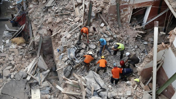 Lebanese and Chilean rescuers search in the rubble of a collapsed building after getting signals there may be a survivor, early Friday, Sept. 4, 2020, in Beirut, Lebanon. A pulsing signal was detected Thursday from under the rubble of a Beirut building that collapsed during the horrific port explosion in the Lebanese capital last month, raising hopes there may be a survivor still buried there. (AP Photo/Hussein Malla)