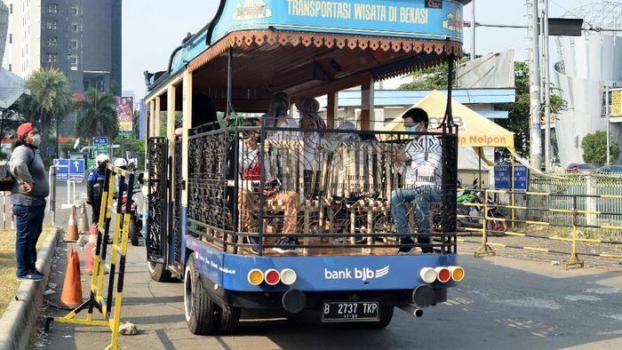 Sejumlah petugas Dinas Perhubungan (Dishub) mengawal bus pariwisata Patriot Kota Bekasi yang akan membawa peserta wisata gratis di Bekasi, Jawa Barat, Minggu (6/9/2020). Kehadiran bus wisata tersebut menjadi sarana transportasi untuk mengenalkan sejumlah lokasi wisata yang ada di Kota Bekasi kepada masyarakat luas. ANTARA FOTO/Suwandy/foc.