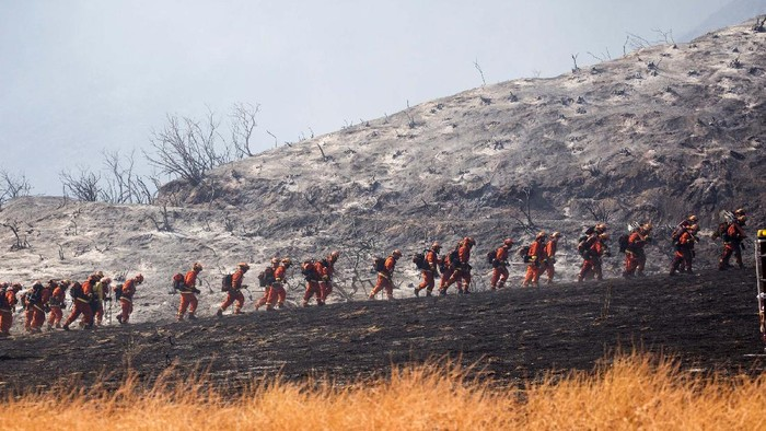 Members of firefighters walk in line during a wildfire in Yucaipa, Calif., Saturday, Sept. 5, 2020. Three fast-spreading California wildfires sent people fleeing Saturday, with one trapping campers at a reservoir in the Sierra National Forest, as a brutal heat wave pushed temperatures into triple digits in many parts of state.(AP Photo/Ringo H.W. Chiu)