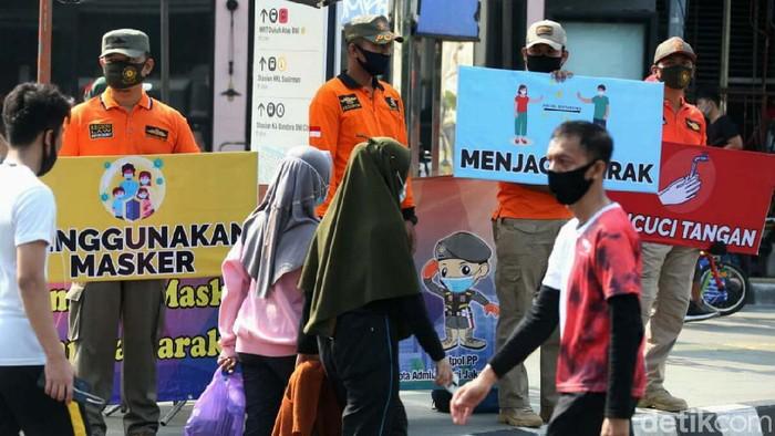 Petugas kepolisian turun langsung ke jalan dalam rangka sosialisasi protokol kesehatan kepada masyarakat. seperti terlihat di Jalan Sudirman-MH Thamrin.