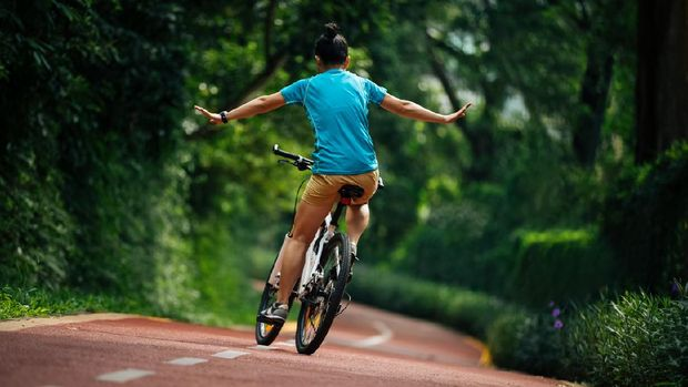 Woman riding a bike on sunny park trail with arms outstretched