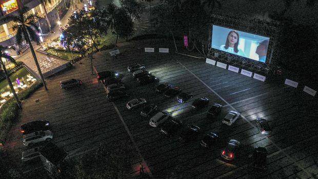 Pengunjung berada di dalam mobil saat menyaksikan film di