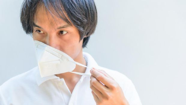 A asian man remove the N95 mask from his face