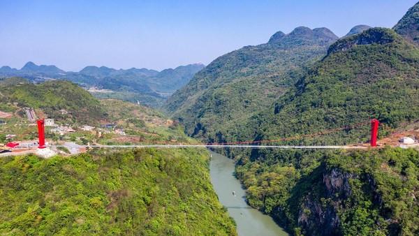 Menara jembatan dan talinya berwarna merah, dengan latar ngarai yang hijau.