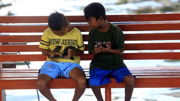 Dua bocah bermain gawai dengan memanfaatkan fasilitas wifi gratis.