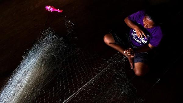 Seorang warga tengah memperbaiki jaring.