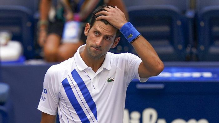 Novak Djokovic, of Serbia, checks a linesman after hitting her with a ball in reaction to losing a point to Pablo Carreno Busta, of Spain, during the fourth round of the US Open tennis championships, Sunday, Sept. 6, 2020, in New York. Djokovic defaulted the match. (AP Photo/Seth Wenig)