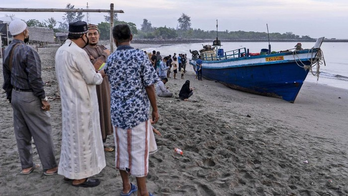 An ethnic Rohingya woman is assisted to walk by others after the boat carrying them landed in Lhokseumawe, Aceh province, Indonesia, early Monday, Sept. 7, 2020. Almost 300 Rohingya Muslims were found on a beach in Indonesias Aceh province Monday and were evacuated by military, police and Red Cross volunteers, authorities said. (AP Photo/Zik Maulana)