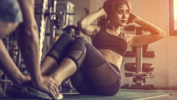 Fitness woman doing sit-ups exercises.Female doing abs workout with personal trainer