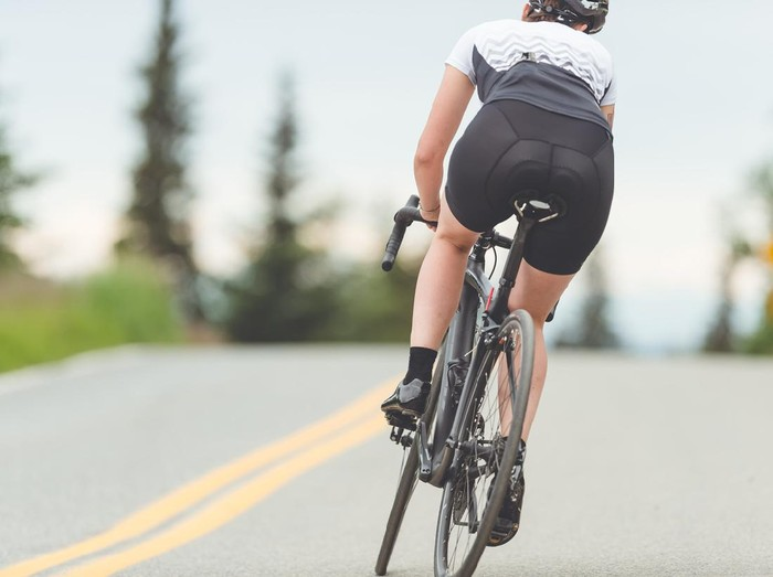 Female cyclist rides along a rural highway on a dry and moderate morning. She is heading up a slight incline. Rear view shot.