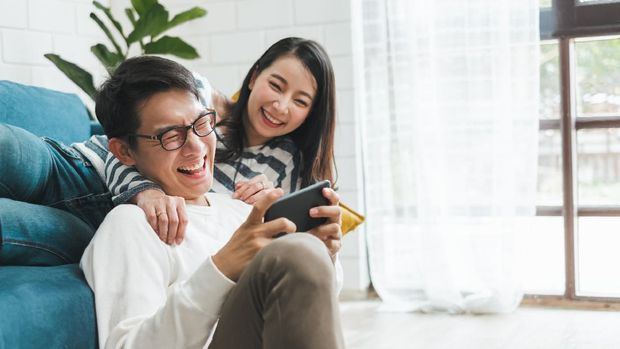 Lifestyle Asian couple man and woman playing game on mobile phone together at home, Asian couple family lifestyle concept