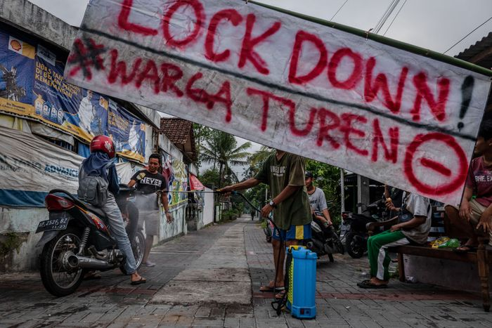 YOGYAKARTA, INDONESIA - MARCH 27:  Villagers spray disinfectant to a motorcyclist as they guard a makeshift barricade blocking the village entrance to prevent the spread of COVID-19 on March 27, 2020 in Yogyakarta, Indonesia. The Indonesia officials has so far confirmed 1.046 cases of the deadly coronavirus in the country with at least 87 recorded fatalities. According to the media and researchers reported the country already has the most deaths in south-east Asia, and estimated that there could be tens of thousands of hidden infections across the country. (Photo by Ulet Ifansasti/Getty Images)