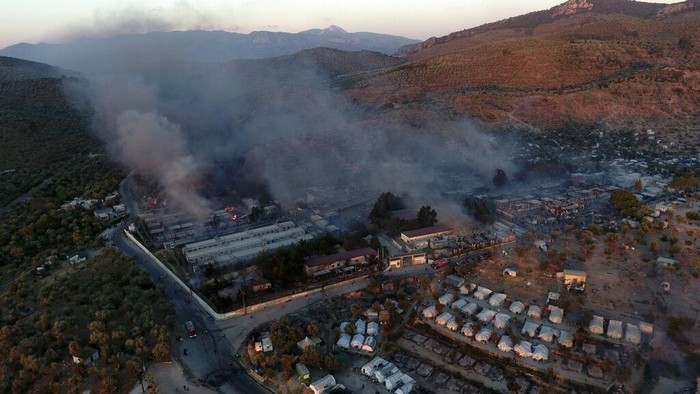 Fire burns container houses and tents in the Moria refugee camp on the northeastern Aegean island of Lesbos, Greece, on Wednesday, Sept. 9, 2020. A fire swept through Greece's largest refugee camp that had been placed under COVID-19 lockdown, leaving more than 12,000 migrants in emergency need of shelter on the island of Lesbos. (AP Photo/Panagiotis Balaskas)