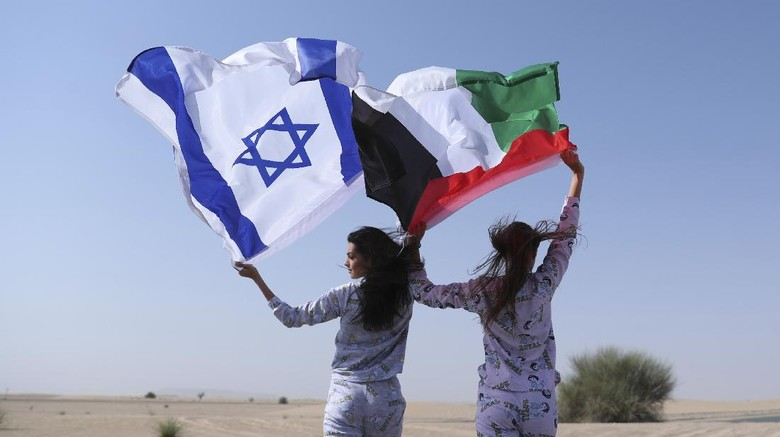 Israeli model May Tager, left, holds Israels blue-and-white flag bearing the Star of David while next to her Anastasia Bandarenka, a Dubai-based model originally from Russia, waves the Emirati flag, during a photo shoot in Dubai, United Arab Emirates, Sunday, Sept. 8, 2020. (AP Photo/Kamran Jebreili)