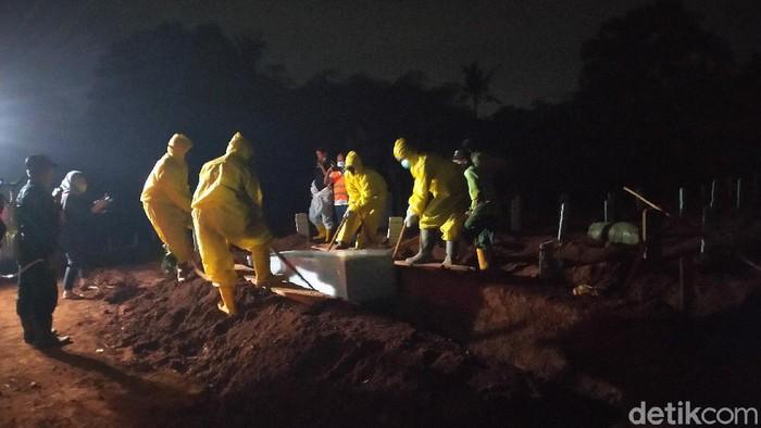 Pemakaman jenazah COVID-19 di TPU Pondok Ranggon malam hari. (Sachril Agustin Berutu/detikcom)