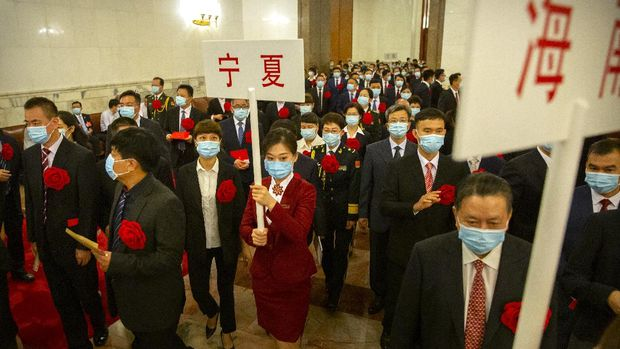 Attendees wearing face masks arrive for an event to honor some of those involved in China's fight against COVID-19 at the Great Hall of the People in Beijing, Tuesday, Sept. 8, 2020. Chinese leader Xi Jinping is praising China's role in battling the global coronavirus pandemic and expressing support for the U.N.'s World Health Organization, in a repudiation of U.S. criticism and a bid to rally domestic support for Communist Party leadership. (AP Photo/Mark Schiefelbein)