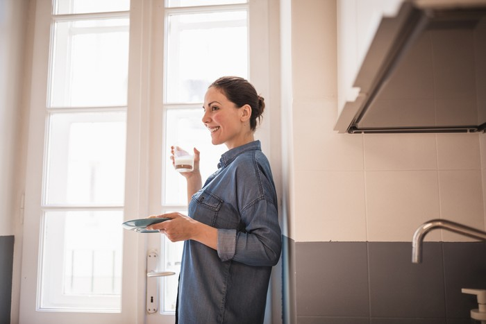 Young woman eating a croissant, drinking fresh milk for breakfast in the kitchen. She is wearing only a blue shirt, standing by the big, bright window