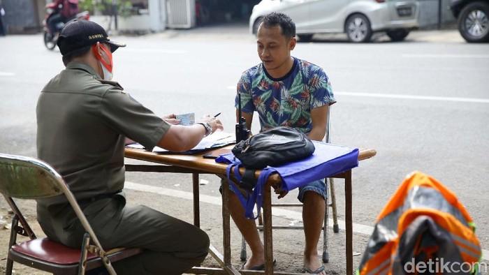 Petugas Satpol PP Kelurahan Bintaro, Jakarta Selatan, melakukan razia masker di tengah tingginya kasus Corona. Sejumlah warga terjaring razia.