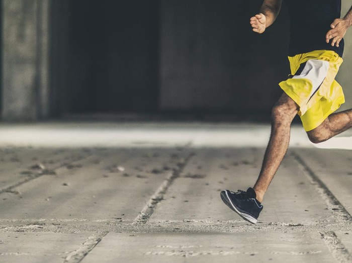Man of african descent running in an empty concrete building