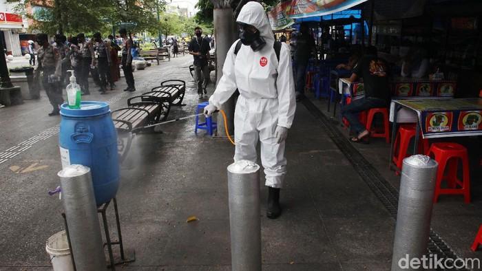 Petugas Kepolisian dari Gegana Polda DIY menyemprotkan cairan disinfektan di jalur pedestrian sepanjang Jalan Malioboro, Yogyakarta, Kamis (10/9/2020).