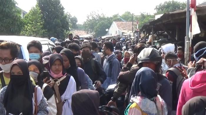 Ribuan pelamar kerja berdesakan di depan pabrik sepatu yang berlokasi di Kecamatan Jatiluhur, Purwakarta. Polisi akhirnya membubarkan kerumunan massa guna menghindari kemungkinan penularan COVID-19.