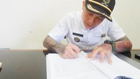 Ditemui detikcom hari ini, Hoho terlihat tengah sibuk di ruang kerjanya. Ia memakai kemeja putih lengan pendek lengkap dengan topi Kades. Di bagian lengan nampak tato dengan motif oriental.
