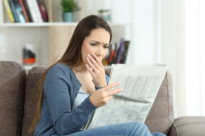 Worried woman reading bad news in a newspaper sitting on a couch in the living room at home