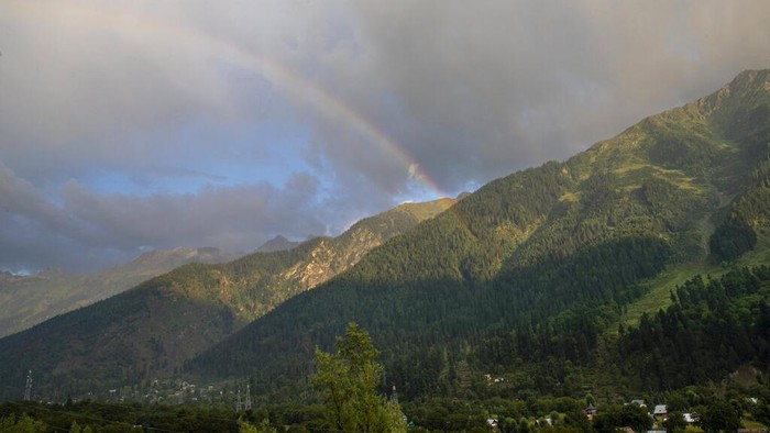A rainbow is seen over the mountains near Gund on Srinagar-Leh highway northeast of Srinagar, Indian controlled Kashmir, Tuesday, Sept. 8, 2020. Bakarwals are nomadic animals herders in Jammu Kashmir state, who wander in search of good pastures for their cattle. (AP Photo/Dar Yasin)