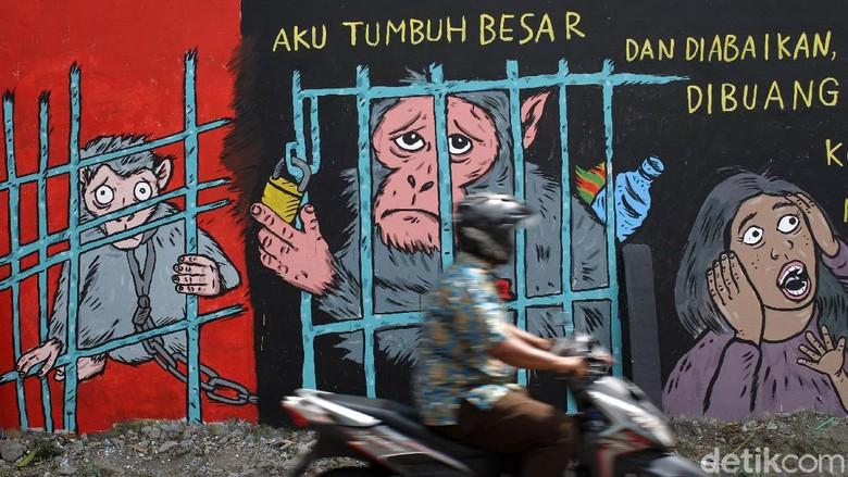 Warga melintas di depan Lukisan mural bertema peduli satwa monyet terpampang di dinding Pasar Satwa dan Tanaman Hias Yogyakarta, Jumat (11/9/2020).