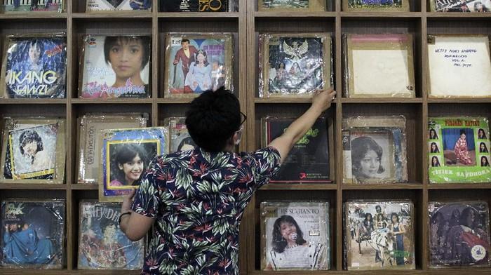 Pegawai RRI Surabaya menunjukkan piringan hitam album lagu lawas di Ruang Restorasi Piringan Hitam di RRI Surabaya, Jawa Timur, Jumat (11/9/2020). Lembaga Penyiaran Publik (LPP) Radio Republik Indonesia (RRI) Surabaya yang memiliki sekitar 8.000  piringan hitam album lagu dari masa ke masa tersebut telah melakukan restorasi atau merekam ulang menjadi digital sebanyak 3.000 piringan hitam album lagu sedangkan selebihnya rusak termakan usia. ANTARA FOTO/Didik Suhartono/foc.