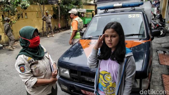 Petugas Satpol PP tertibkan masyarakat yang tak mengenakan masker. Sanksi itu akan diberikan tak hanya untuk orang dewasa tetapi juga anak-anak.