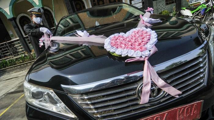 Pengantin menggunakan mobil dinas Pemerintah Kota Bekasi untuk menuju lokasi pernikahan di Bekasi, Jawa Barat, Sabtu (12/9/2020). Wakil Walikota Bekasi menyediakan fasilitas gratis mobil dinas pada hari Sabtu dan Minggu untuk antar jemput warga yang akan melaksanakan pernikahan saat pandemi COVID-19. ANTARA FOTO/ Fakhri Hermansyah/hp.