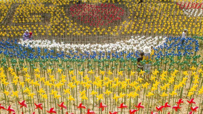 Taman Kincir Angin Marigold Garden di Karawang jadi alternatif destinasi wisata di akhir pekan. Di sana warga dapat berfoto dengan latar ribuan kincir angin.