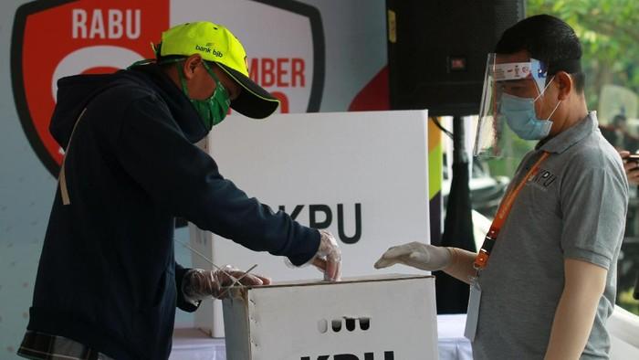 Petugas Kelompok Penyelenggara Pemungutan Suara (KPPS) dengan menggunakan alat pelindung diri (APD) mengawasi pemilih di bilik suara khusus saat simulasi pemungutan suara dengan protokol kesehatan pencegahan dan pengendalian COVID-19 di TPS 18 Cilenggang, Serpong, Tangerang Selatan, Banten, Sabtu (12/9/2020). KPU akan menyiapkan satu bilik suara khusus di setiap TPS yang diperuntukan bagi pemilih yang suhu tubuhnya diatas 37 derajat saat pemungutan suara Pilkada serentak 2020. ANTARA FOTO/Muhammad Iqbal/pras.