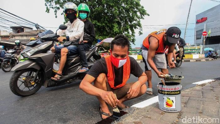 Razia masker masih terus dilakukan di kawasan Ibu Kota. Warga yang melanggar akan dikenakan sanksi beragam, mulai menyapu jalan hingga mengecat pembatas jalan.