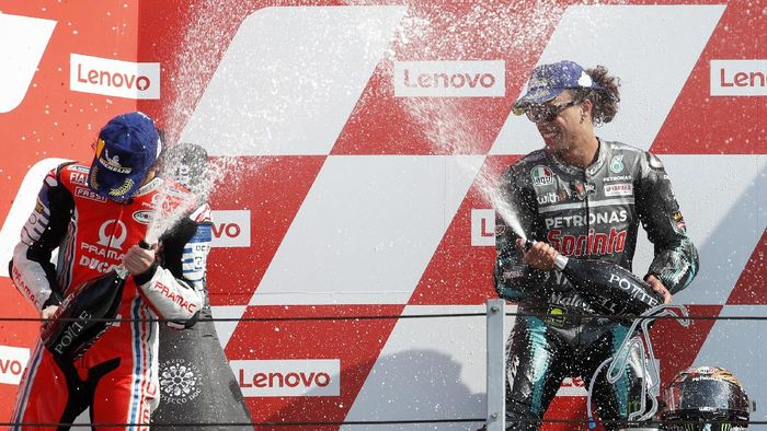 Second placed Francesco Bagnaia, left, and winner Franco Morbidelli, both of Italy, spray each other on the podium of the MotoGP race of the San Marino Motorcycle Grand Prix at the Misano circuit in Misano Adriatico, Italy, Sunday, Sept. 13, 2020. (AP Photo/Antonio Calanni)