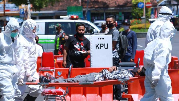 Petugas kesehatan menyemprotkan cairan disinfektan di Tempat Pemungutan Suara saat simulasi Pemilihan Kepala Daerah di Banyuwangi, Jawa Timur, Senin (14/9/2020).  Simulasi tersebut digelar untuk menyiapkan segala hal yang diperlukan untuk penyelenggaraan Pilkada serentak pada 9 Desember 2020 di tengah wabah COVID-19. ANTARA FOTO/Budi Candra Setya/wsj.