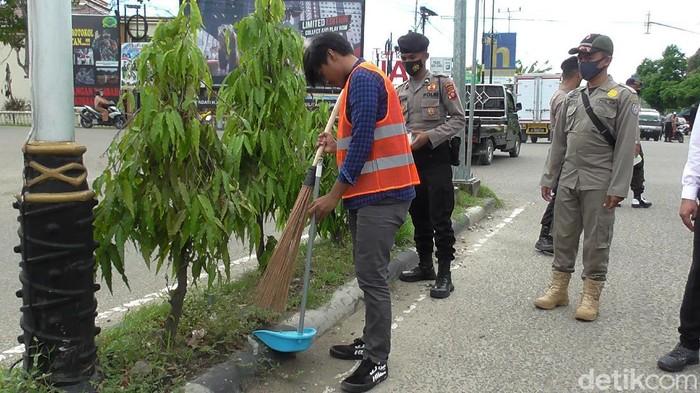Warga tak bermasker di Gorontalo dihukum menyapu jalan.