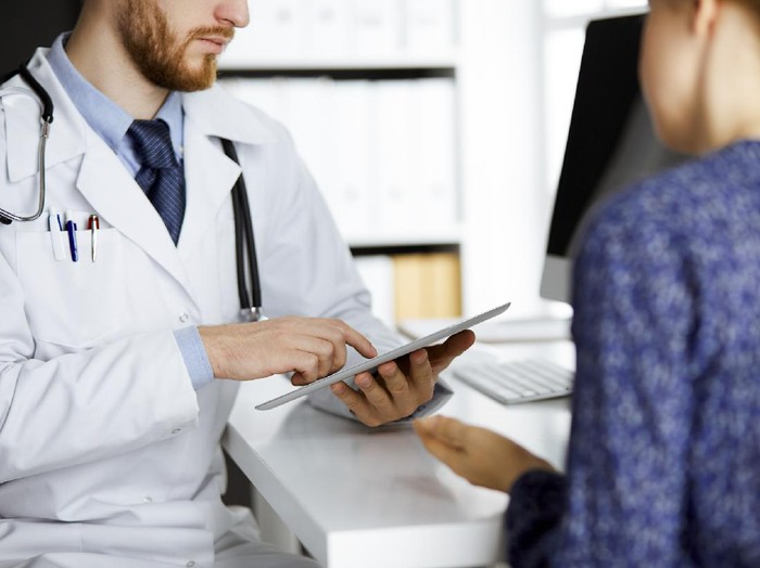 Unknown red-bearded doctor and patient woman discussing current health examination while sitting and using tablet computer in clinic, close-up. Medicine concept.