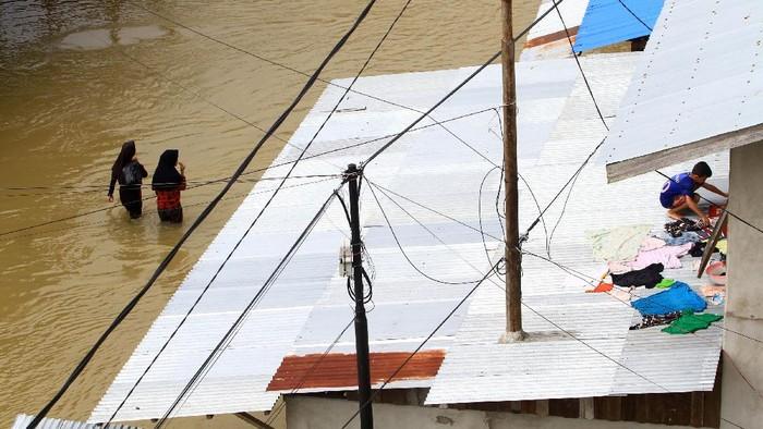 Seorang anak menjemur baju di atap rumahnya yang tergenang banjir di Jalan Ngurah Rai, Putussibau, Kabupaten Kapuas Hulu, Kalimantan Barat, Selasa (15/9/2020). Kota Putussibau masih terendam banjir dan mengalami pemadaman listrik serta jaringan telekomunikasi sejak Minggu (13/9/2020). ANTARA FOTO/Jessica Helena Wuysang/foc.