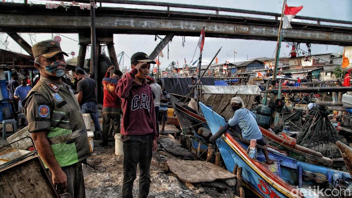 Razia masker terus dilakukan di tengah penerapan PSBB ketat di Ibu Kota. Kawasan Kampung Nelayan Cilincing pun tak luput dari sasaran operasi tertib masker.