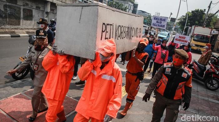 Petugas PPSU mengarak peti mati di kawasan Tanah Abang, Jakarta Pusat, Selasa (15/9/2020). Aksi teatrikal ini untuk mengingatkan bahaya COVID-19.