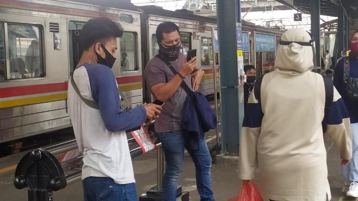 Penumpang KRL di Stasiun Tanah Abang masih menggunakan masker scuba dan masker buff